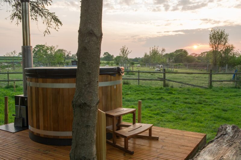 Enjoy the views across the fields from the wood fired hot tub
